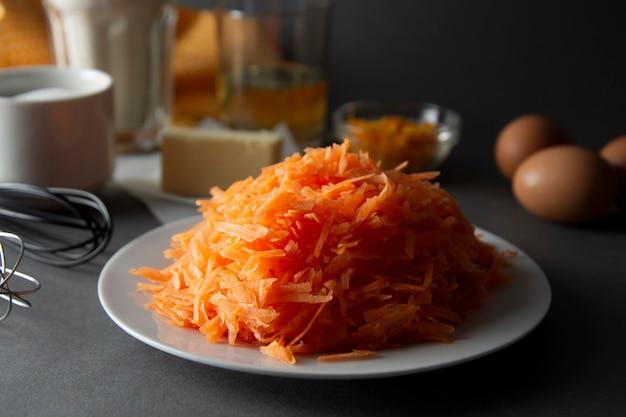 Carottes hachées pour gâteau aux carottes, tartes ou muffins. ingrédients pour cuisiner la tarte aux carottes ou un gâteau.