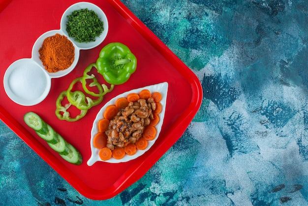 Carottes, haricots et légumes en tranches sur une assiette sur un plateau, sur la table bleue.