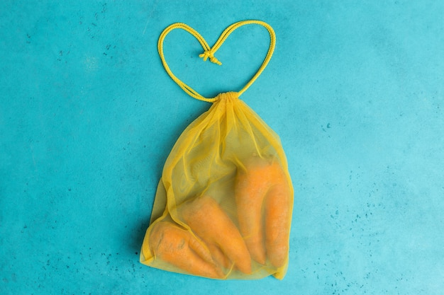 Carottes laides à la mode en sac en filet réutilisable écologique jaune concept créatif shopping zéro déchet.