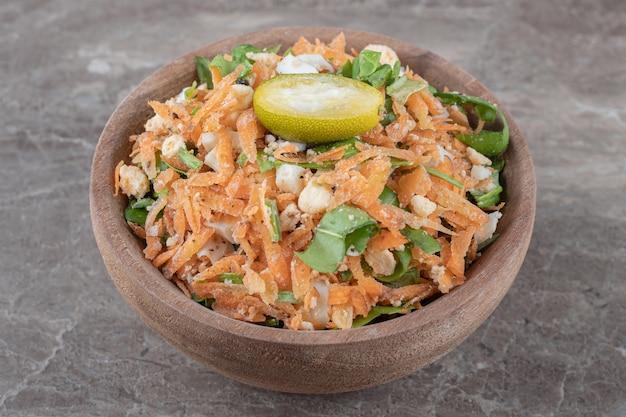 Carottes en dés et salade de légumes dans un bol en bois.