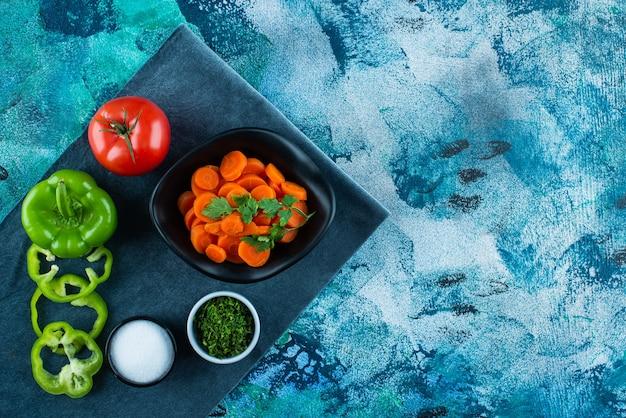 Carottes tranchées dans un bol à côté de légumes sur une serviette , sur la table bleue.
