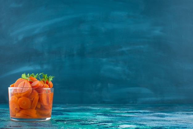Carottes tranchées dans un verre , sur la table bleue.