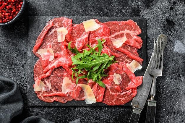 Carpaccio de bœuf italien avec salade de roquette, parmesan. fond noir. vue de dessus.