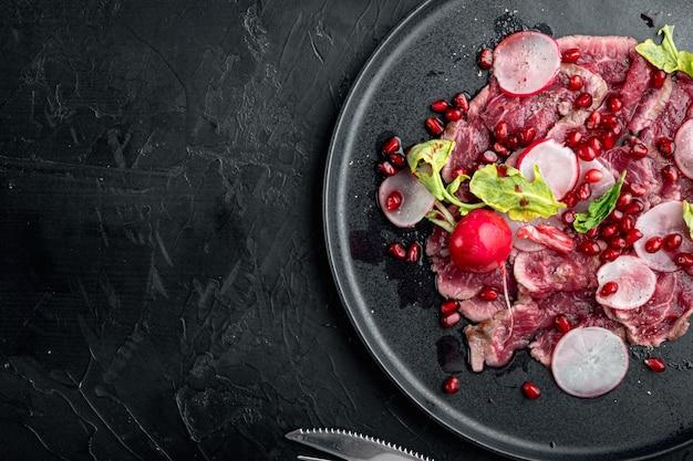 Carpaccio de boeuf marbré, radis et grenat, sur assiette, sur pierre noire