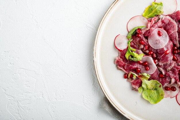 Carpaccio de boeuf marbré, avec radis et grenat, sur assiette, sur table en pierre blanche, vue de dessus à plat