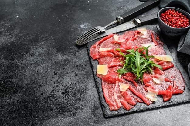 Carpaccio de boeuf sur plaque noire avec parmesan et roquette