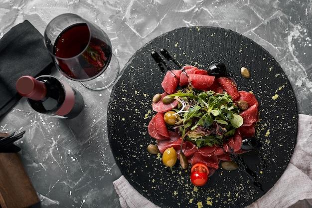 Carpaccio de boeuf à la roquette sur une plaque noire, cuisine italienne traditionnelle