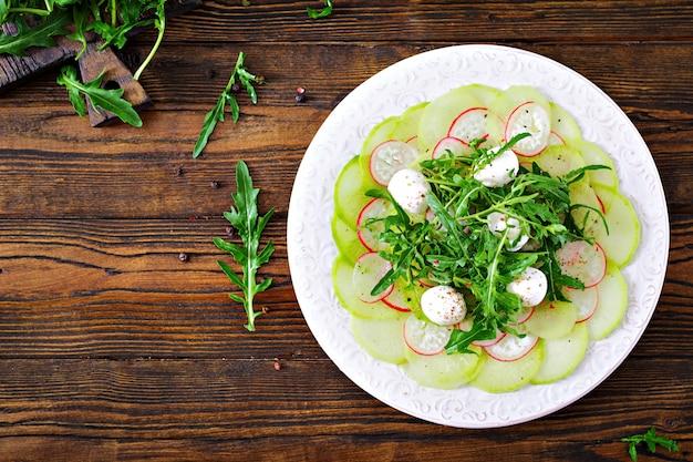 Carpaccio de radis avec roquette, mozzarella et sauce. la nourriture saine. salade daikon. haut