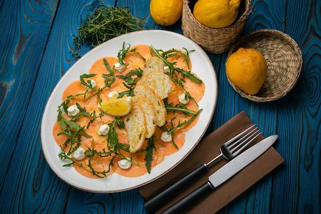 Carpaccio de saumon sur une assiette aux citrons, roquette, fromage de chèvre et croûtons