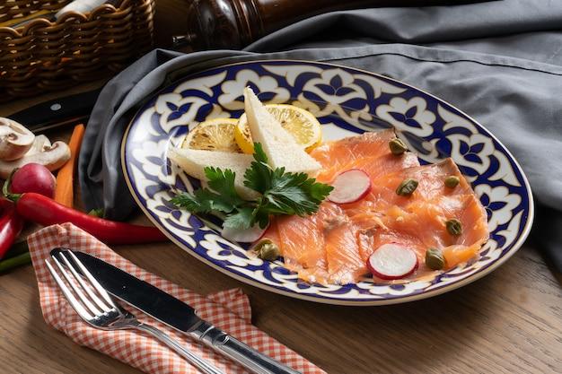 Carpaccio de saumon aux câpres, radis et citron sur une assiette avec un traditionnel ouzbek