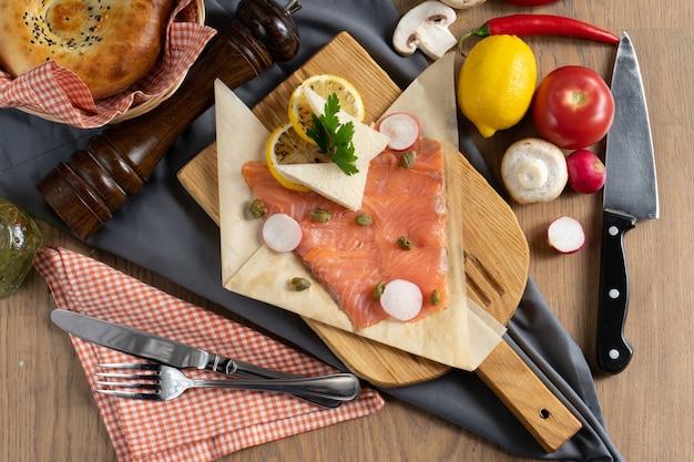 Carpaccio de saumon aux câpres, radis et citron sur une planche à découper en bois