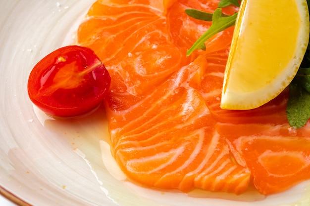 Carpaccio de saumon servi avec citron et roquette
