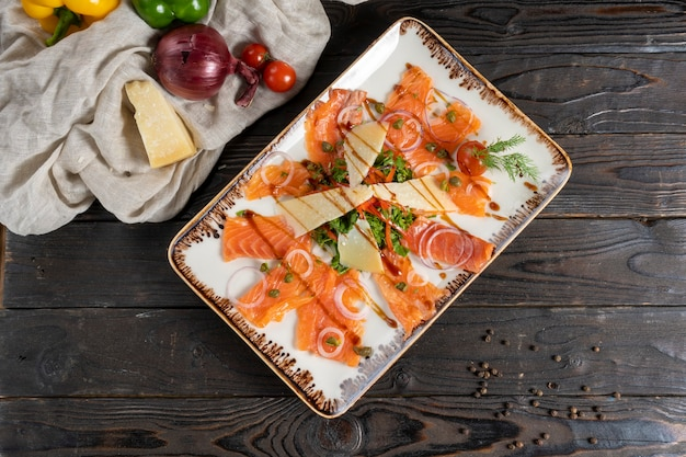 Carpaccio de saumon ou de truite aux herbes, câpres, oignons et fromage