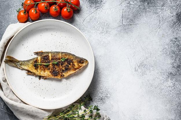 Carpe carassin frit sur une plaque blanche. poissons biologiques de rivière. fond gris. vue de dessus. espace pour le texte