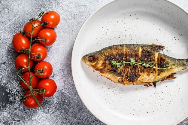 Carpe carassin grillé sur une plaque blanche. poissons biologiques de rivière. fond gris. vue de dessus