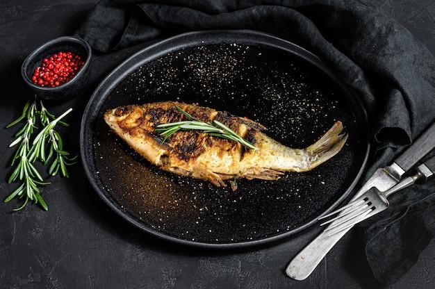 Carpe carassin grillé sur une plaque blanche. poissons biologiques de rivière. fond noir. vue de dessus
