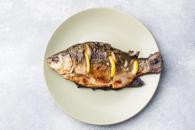 Carpe de poisson au four avec citron vert sur une assiette.
