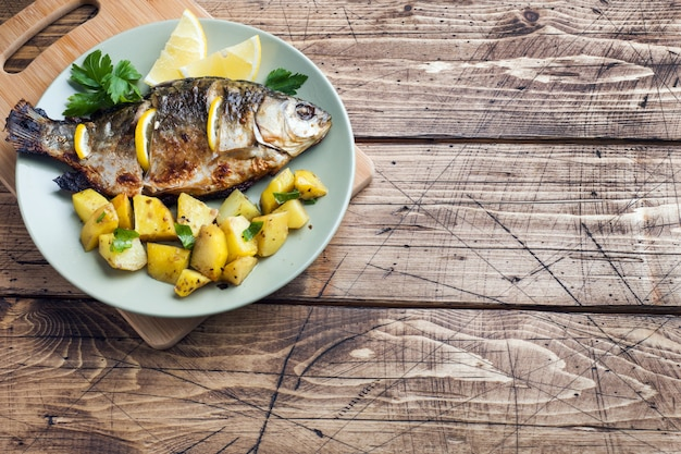Carpe de poisson au four avec citron vert et pommes de terre sur une assiette. en bois. fond