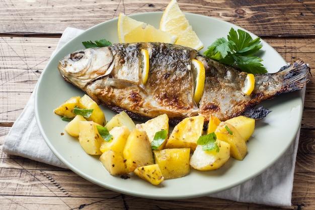 Carpe de poisson au four avec citron vert et pommes de terre sur une assiette. en bois.
