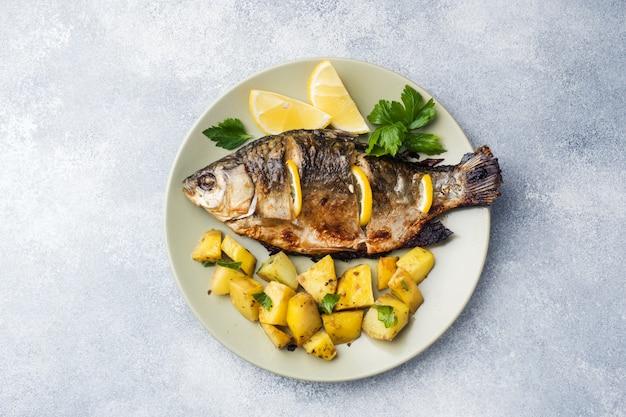Carpe de poisson au four avec citron vert et pommes de terre sur une assiette. espace de copie