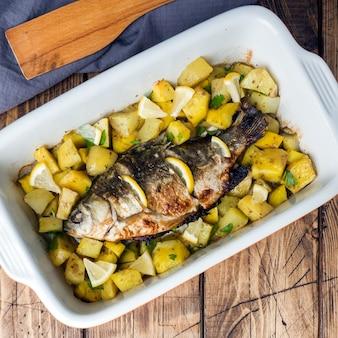 Carpe de poisson au four avec pommes de terre dans une poêle en céramique. style rustique. fond