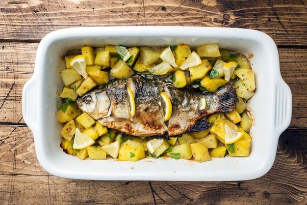 Carpe de poisson au four avec pommes de terre dans une poêle en céramique. style rustique.