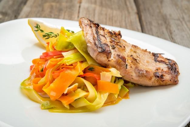 Carpe de poisson frit et salade de légumes frais sur fond en bois.