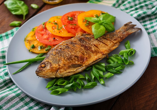 Carpe de poisson frit et salade de légumes frais sur table en bois.