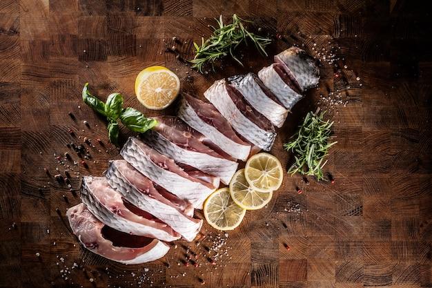 Carpe de poisson en portions avec sel poivre citron et herbes sur planche de cuisine.