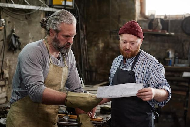 Carpenter discutant du plan avec le maître avant de commencer le travail dans l'atelier
