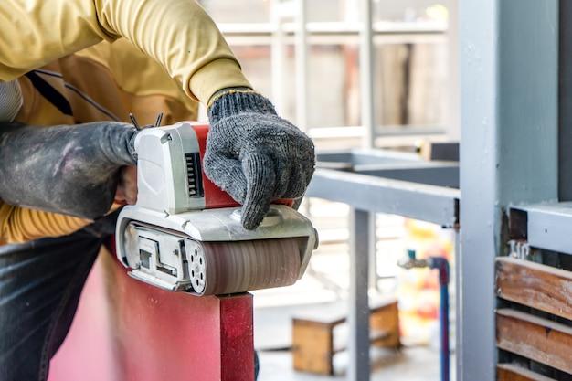 Carpenter rase la porte en bois rouge par sa machine à raser dans un champ extérieur avec un environnement de structure de bâtiment en acier.