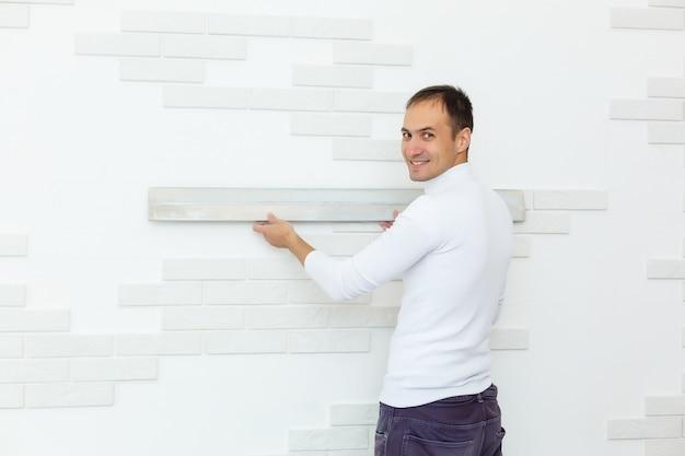 Carpenter utilisant le niveau à bulle contre le mur de briques rouges