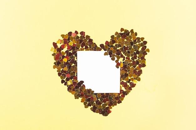 Carré blanc pour les notes entourées d'étincelles jaunes en forme de carte cœur