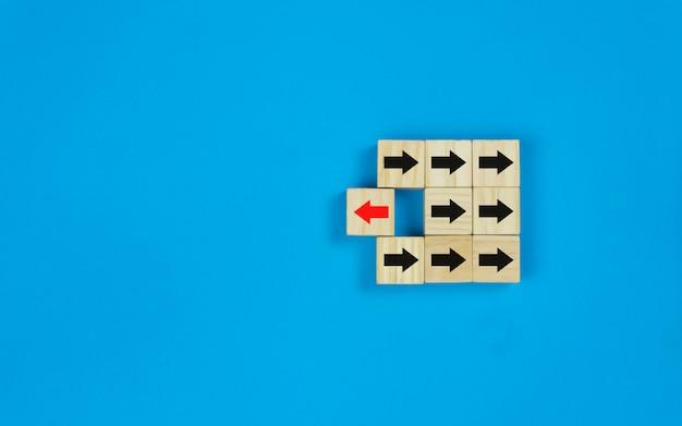 Un carré de bois bloque le symbole de la flèche rouge et se tourne dans le sens opposé du symbole des flèches noires.