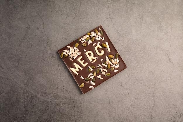 Carré de chocolat noir avec du chocolat blanc note de remerciement sur fond sombre
