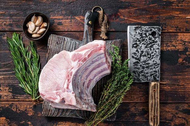 Carré cru de côtelettes de longe de porc avec des côtes sur une planche de boucher avec couperet à viande