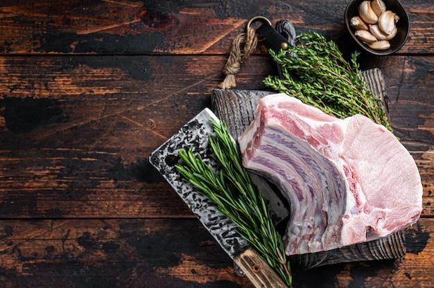 Carré cru de côtelettes de porc avec côtes levées sur une planche de boucher avec couperet à viande.