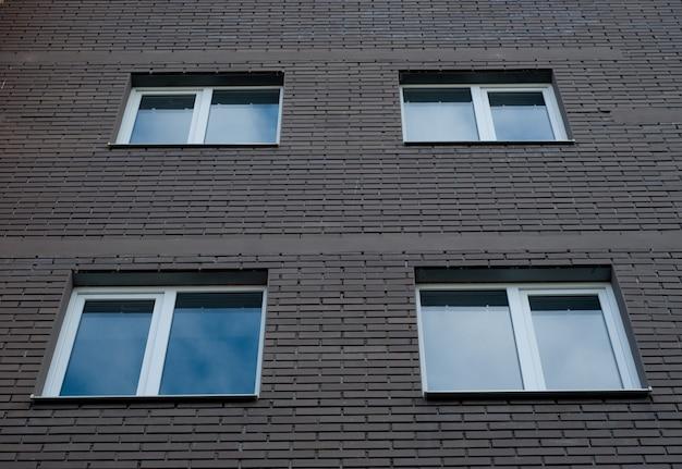 Carré, fenêtres en plastique sur la façade d'un nouveau bâtiment