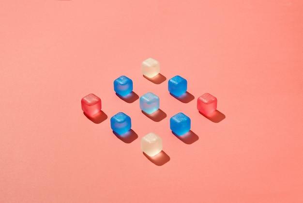 Carré géométrique de glaçons colorés en plastique avec des ombres dures