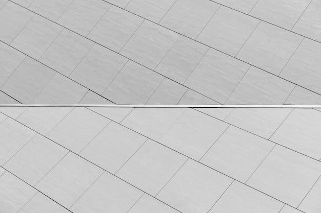 Carreau gris clair avec joint sur fond de mur pour extérieur.
