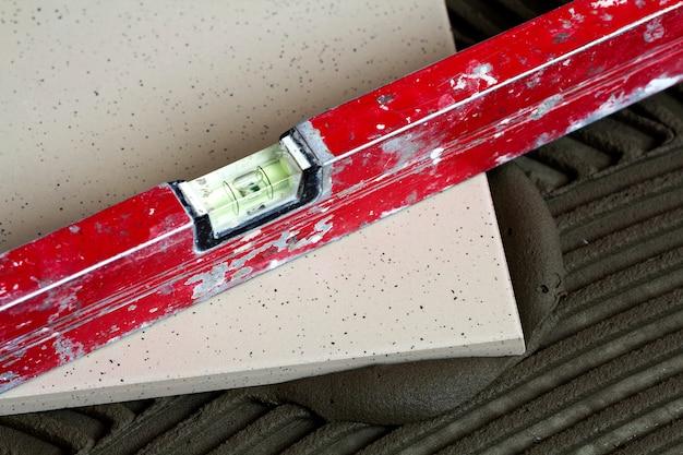 Carreaux de céramique et outils pour carreleur. installation de carreaux de sol. amélioration de l'habitat, rénovation - colle à carrelage, mortier, niveau.