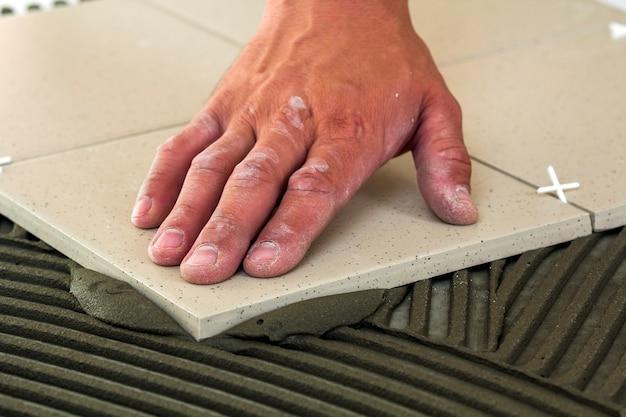 Carreaux de céramique et outils pour carreleur. main de travailleur installant des carreaux de sol. amélioration de l'habitat, rénovation - colle à carrelage, mortier.