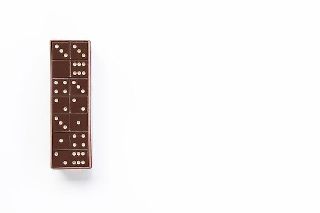 Carreaux de dominos noirs vintage dans la boîte sur fond blanc