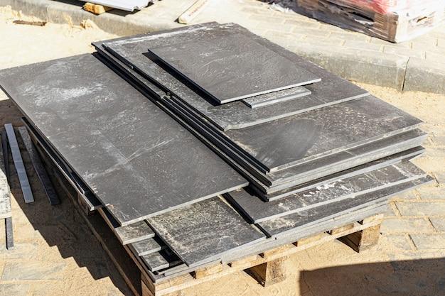 Carreaux de grès cérame sur une palette sur un chantier de construction. restes de tuiles après la pose du sol.