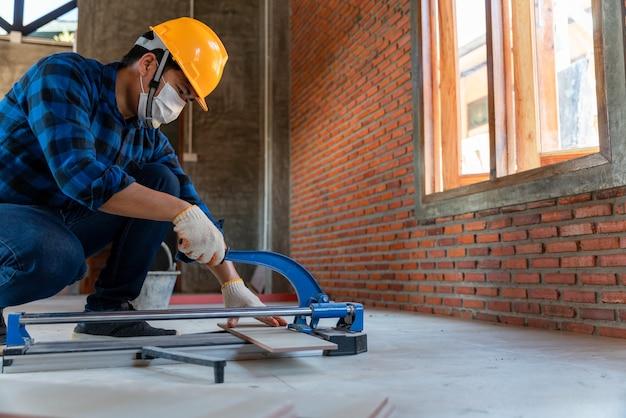 Carreleur artisanal, ouvrier carreleur industriel travaillant avec un équipement de coupe de carreaux de sol sur un chantier de construction