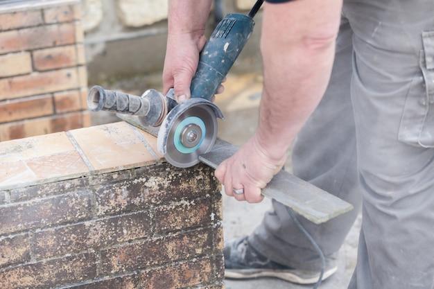 Carreleur couper une tuile avec un moulin