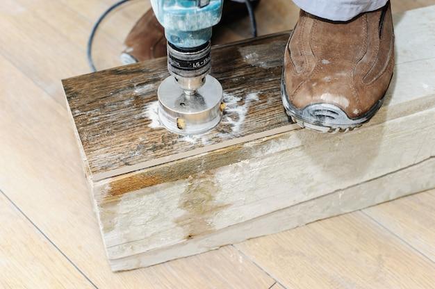 Carreleur sculpte un trou dans la tuile.