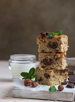 Carrés d'avoine avec du chocolat et une tasse de lait. barres diététiques. boulangerie saine pour le petit déjeuner ou le dessert.