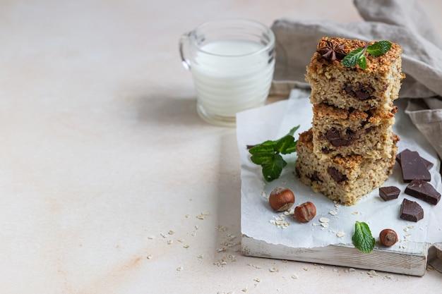Carrés d'avoine avec du chocolat et une tasse de lait. barres diététiques. petit-déjeuner ou dessert sain.