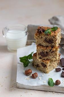 Carrés d'avoine avec du chocolat et une tasse de lait. petit-déjeuner ou dessert sain.